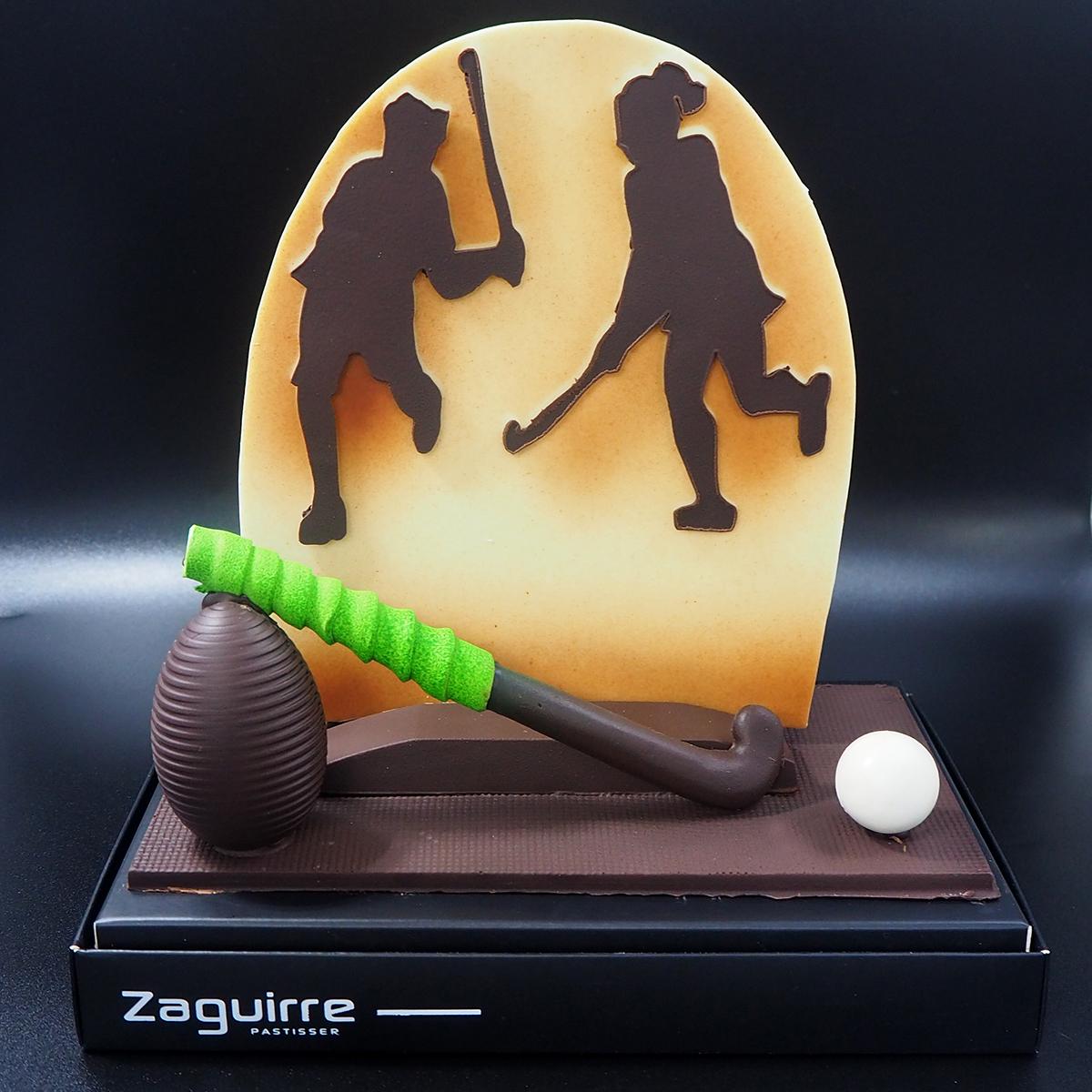 Mona de pascua de chocolate con jugador y jugadora de hockey hierba
